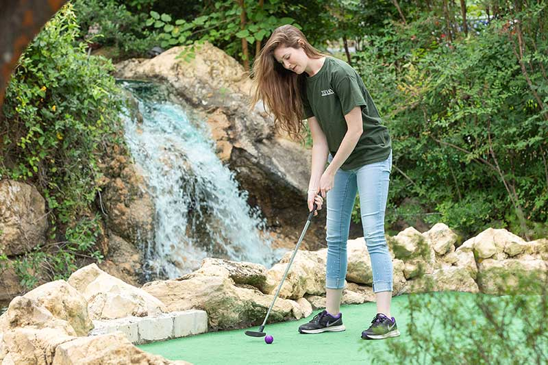 teen girl playing mini golf