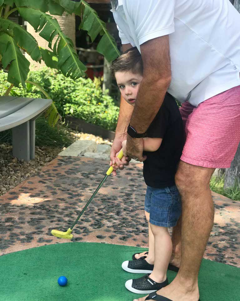 little boy playing mini golf with dad